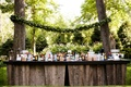 Wood bar at outdoor cocktail hour between trees garland with moss monogram in between trees