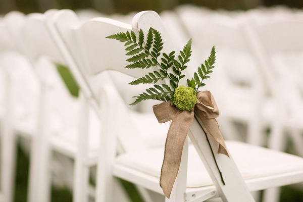 Green fern tied to white ceremony chair with brown ribbon outdoor vineyard wedding