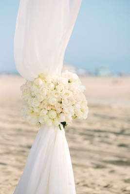 Beach wedding ceremony with white rose tiebacks on ceremony canopy of white fabric