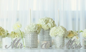 White wedding reception with white hydrangeas in beaded glass vases and crystal Mr & Mrs signs