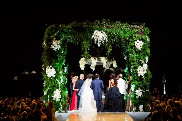 wedding ceremony jewish wedding under greenery chuppah white flowers after sundown night ceremony