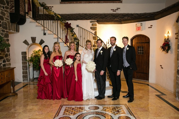 Holiday wedding with bridesmaids in red dresses hold white rose bouquets, bride in Pnina Tornai