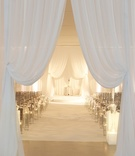 All-white wedding ceremony with chiffon drapery and candles