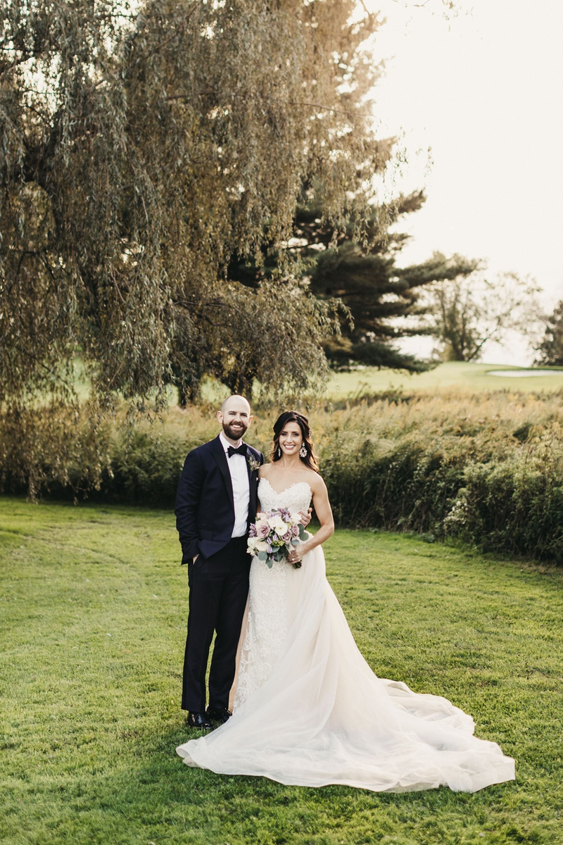 wedding portrait with bride in nicole spose lace dress in overskirt, groom in midnight blue tux