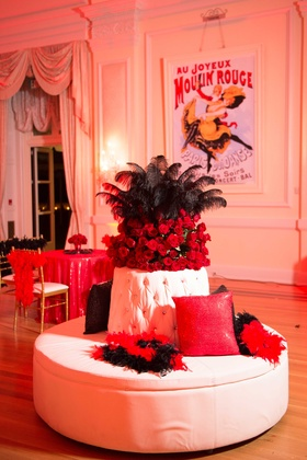 Moulin Rouge theme wedding after party with black feather boas, red roses, red linens, posters