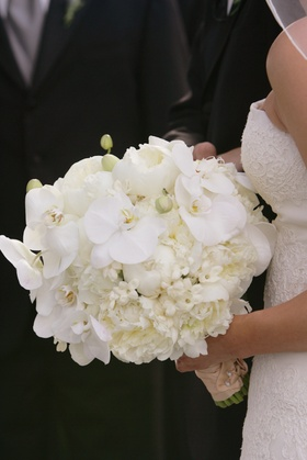 Bride holding white flower bouquet with orchid, peony, and stephanotis blooms