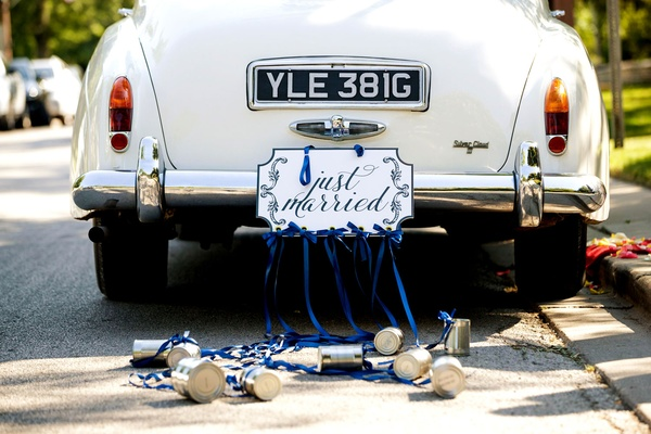 Classic white car with just married sign and cans trailing behind with blue ribbon