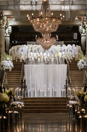 wedding ceremony stage floating candles white drapery orchid flowers in halo wreath over vow spot