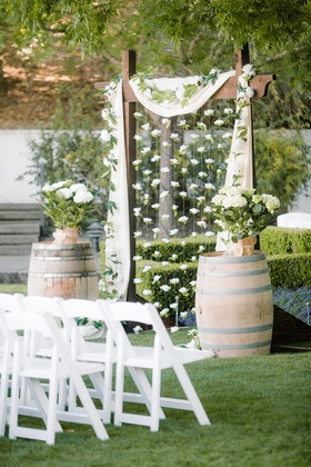 Outdoor wedding ceremony with wooden arch, strings of gardenias, and potted hydrangeas on barrels