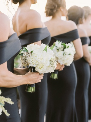 Bridesmaids holding white rose bouquets accented with greenery off shoulder black gowns