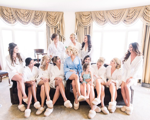 Bride in light blue robe with bridesmaids in white robes all in matching slippers