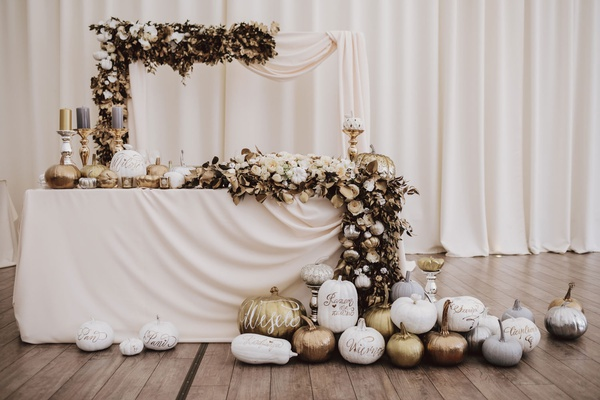 fall wedding ideas sweetheart table arch garland gold silver white pumpkins candlesticks draped