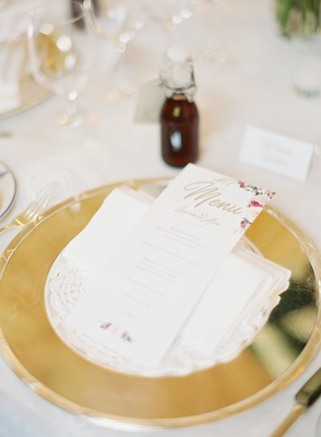 wedding place setting gold charger plate flower print menu card sloe gin on tables wedding favors