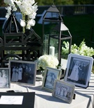 black and white pictures from family members weddings displayed in frames on guestbook table flowers