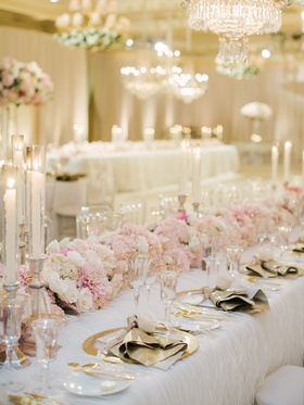 Wedding reception table with floral runner of pink, white roses, hydrangeas, dahlias