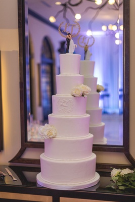 White six layer tier wedding cake with fresh flowers and classic cake topper in front of mirror