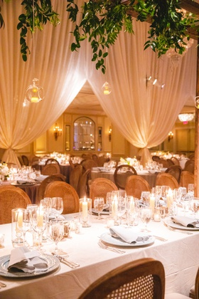 wedding reception greenery glass orb candles overhead long table wood cane chairs candles low flower