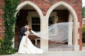 Bride and groom kiss as cathedral veil floats in wind