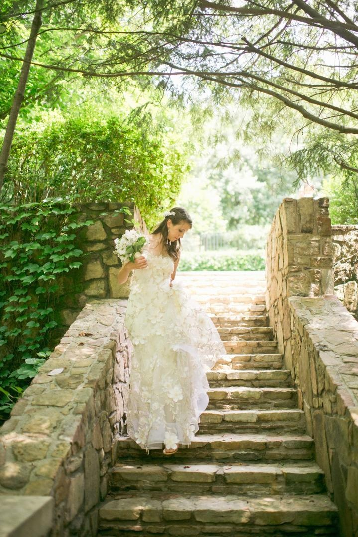 Bride walks on stone steps with flower motif dress