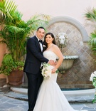 Bride in Monique Lhuillier strapless wedding dress with ivory bouquet and pearl necklace groom