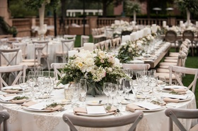 Outdoor wedding reception round table with low centerpiece peony ranunculus greenery rustic elegant