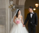 Bride in Kenneth Pool ball gown and groom in tuxedo holding hands