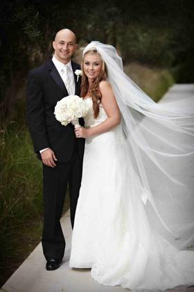 Wedding portrait full length with tuxedo groom and veil bride