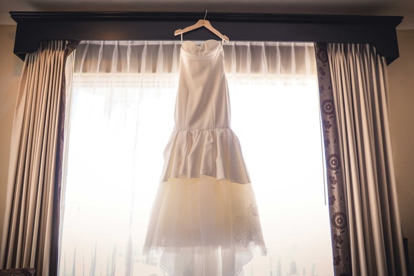 a brides form fitting white trumpet wedding dress hanging before the ceremony
