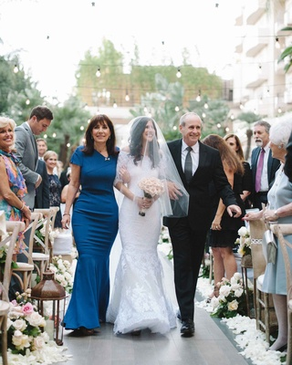 Bride in Marchesa mermaid wedding dress walks down aisle with blue mother of the bride dress