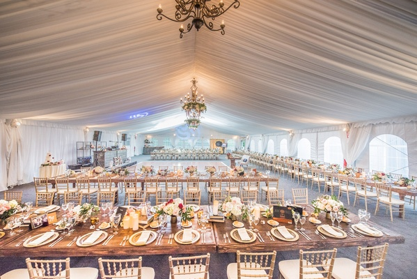wedding reception space farm tables gold chiavari chairs white drapery ceiling floral chandeliers