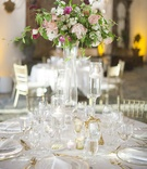 Wedding reception round table gold flatware and charger plate tall centerpiece in glass vase candles