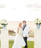 Bride and groom in white at ocean lawn destination wedding ceremony white risers hydrangea flowers