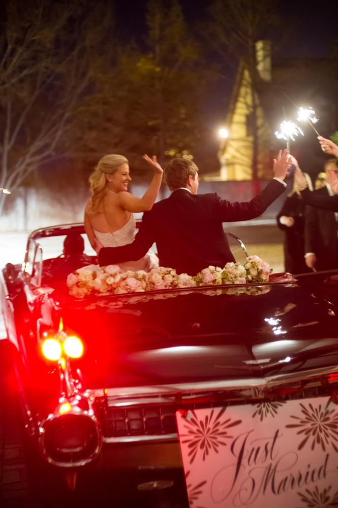 Bride and groom drive away from reception on top of convertible