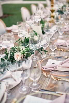 long wooden table with blush table runner & garland with floating candles