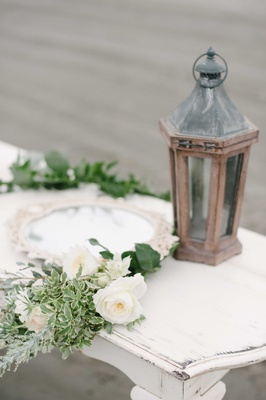 mirror with white frame old brown lantern and lush green garland on white table