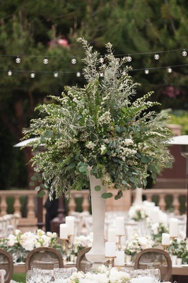 Tall greenery wedding centerpiece white flowers and green leaves white vase gold candlestick