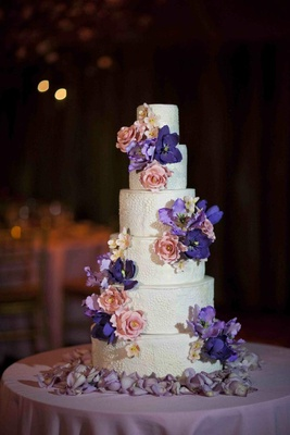 White wedding cake with textured surface decorated with pink and purple flowers