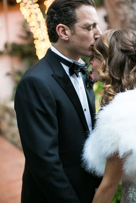 Bride in wedding dress and white fur stole wrap smiles as groom in tuxedo kisses her forehead