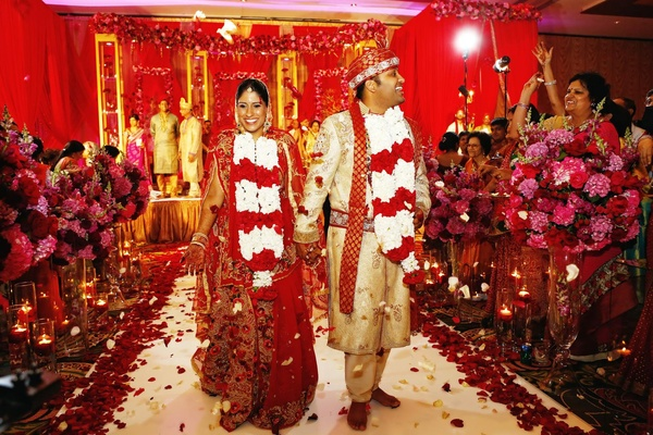Bride in a red lehenga with gold embroidery with groom in gold sherwani with red embroidery