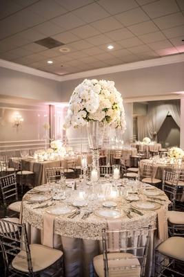 Round wedding reception table textured linens tall centerpiece crystals orchids glass vase
