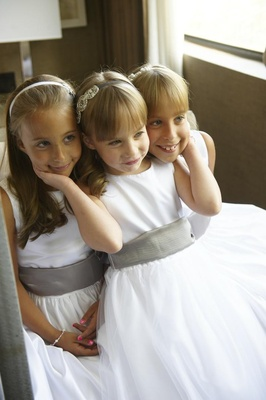Three flower girls with bangs and grey sashes on white dresses