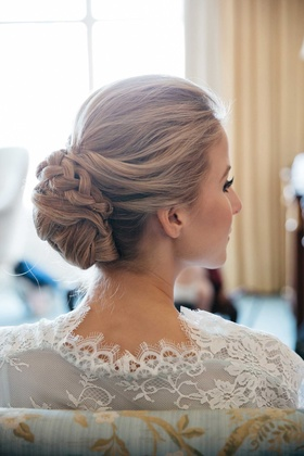 Bride in white lace robe with hair pulled back into updo with braid