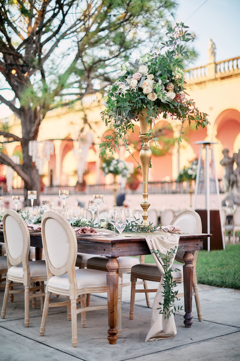 wooden wedding reception table with blush runner covered in greenery