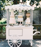 Wedding reception Paris theme dessert pastry cart with three cakes and macaron sphere with pastries
