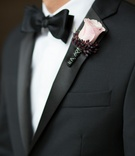 Groom in tuxedo with pink rose boutonniere and black silver ribbon