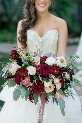 wide bridal bouquet with scarlet dahlias, blush and ivory roses, and eucalyptus