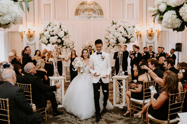 wedding ceremony ballroom white pink rose hydrangea flowers flower petal toss guests in gold chairs