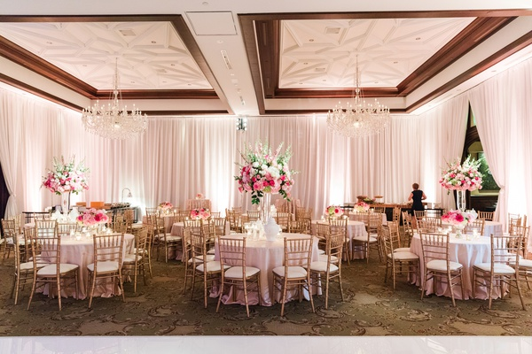 wedding reception with gold chiavari chair, bright pink floral centerpieces, chandeliers