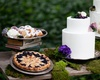 Outdoor wedding reception dessert table with teacakes, berry pie and white wedding cake
