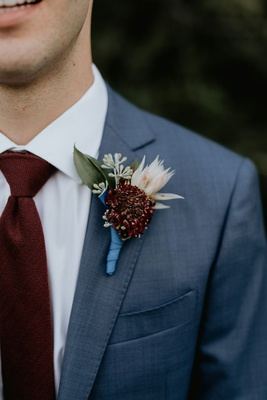 wedding attire groom boutonniere blue ribbon burgundy flower blush flower greenery suit burgundy tie